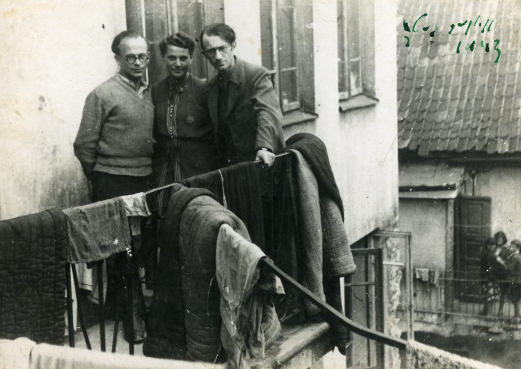 Three people stand on a balcony in the Vilna ghetto
