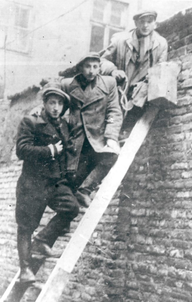 Black and white photograph of three men up a ladder in the Warsaw Ghetto