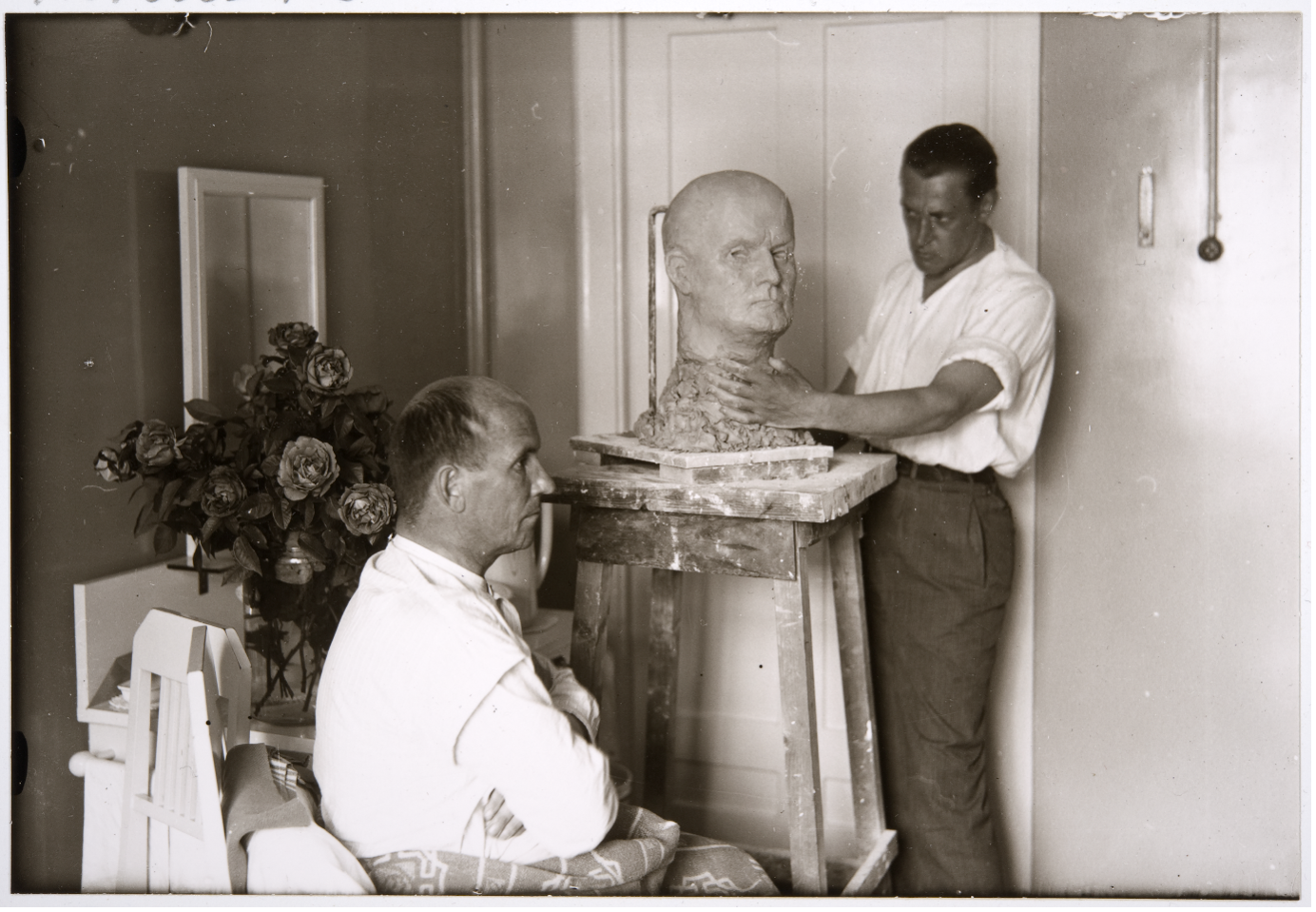A man poses whilst an artist creates a sculpture of him
